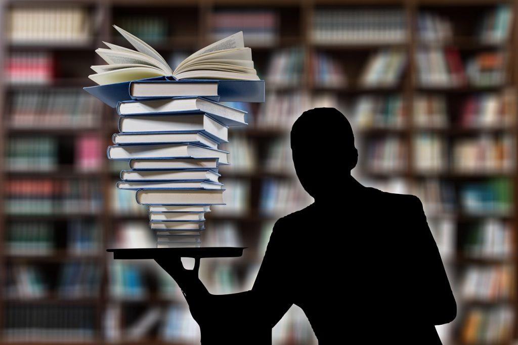 grafika przedstawiająca kontur postaci trzymającej w jednej ręce stos książek, w tle rozmyte regały z książkami
