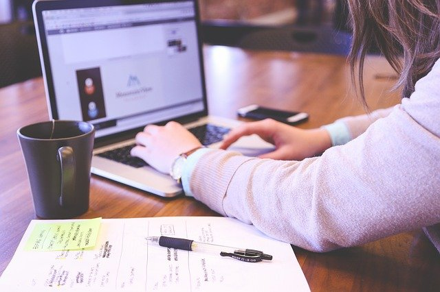 zbliżenie na ręce osoby pracującej na laptopie, obok kubek z kawą i dokumenty
