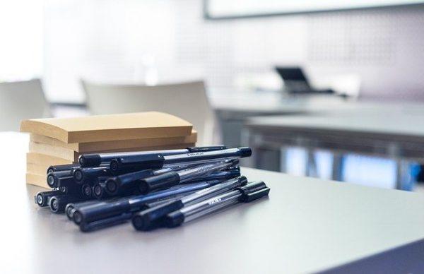 kolorowe zdjęcie: sala wykładowa, na jednym ze stolików leżą długopisy niebieskie oraz karteczki samoprzylepne