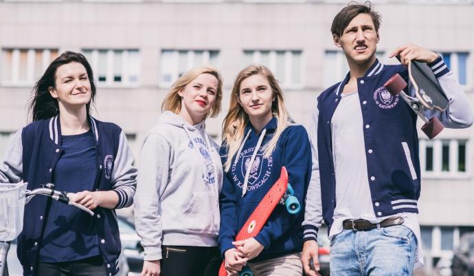 kolorowe zdjęcie: czwórka młodych ludzi, patrzących w obiektyw, ubranych w ubrania z logo UŚ