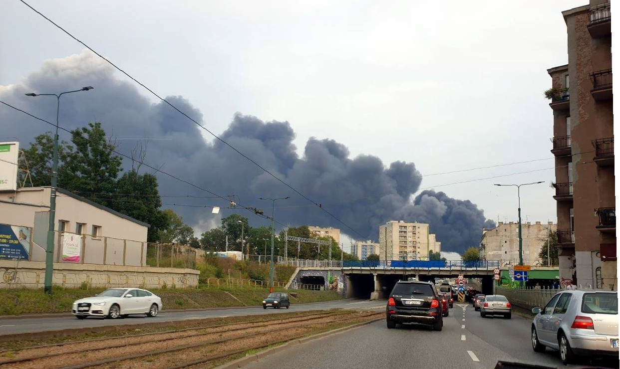 samochody wjeżdżające pod most, w tle ponad budynkami kłęby dymu