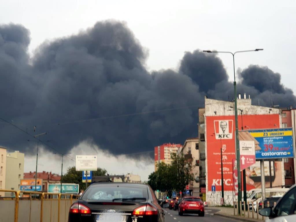 widok z samochodu jadącego ulicą, po prawej stronie budynki nad którymi unoszą się kłęby dymu