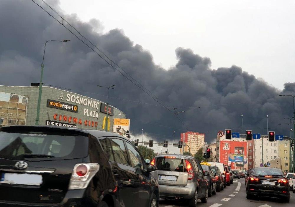 samochody stojące na czerwonym świetle, w oddali widać kłęby gęstego dymu