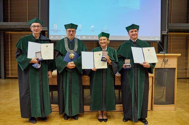 trzech mężczyzn i kobieta ubrani w zielone togi prezentują dyplomy