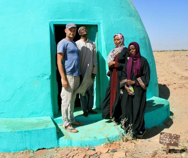 Grupa ludzi stojąca przy afrykańskim domu o turkusowym kolorze ścian