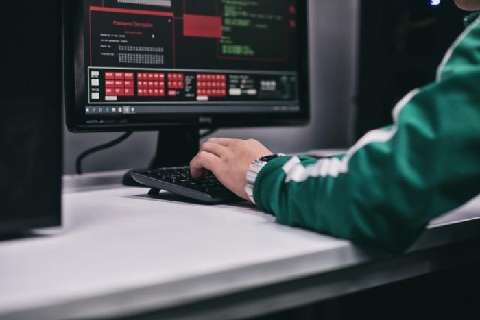 Monitor i dłoń na klawiaturze