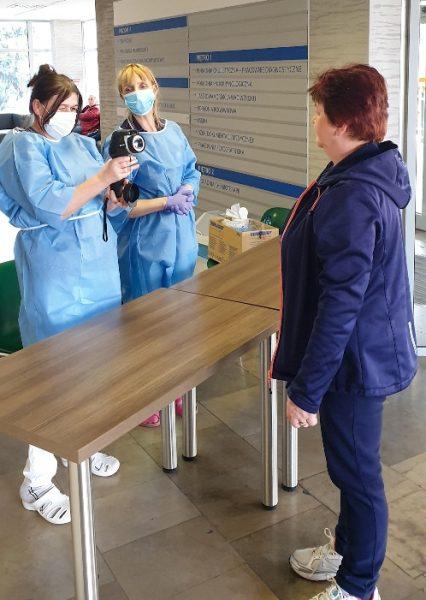 Dwie kobiety trzymają kamerę termowizyjną skierowaną w stronę trzeciej osoby, fot. Joanna Chłądzyńska