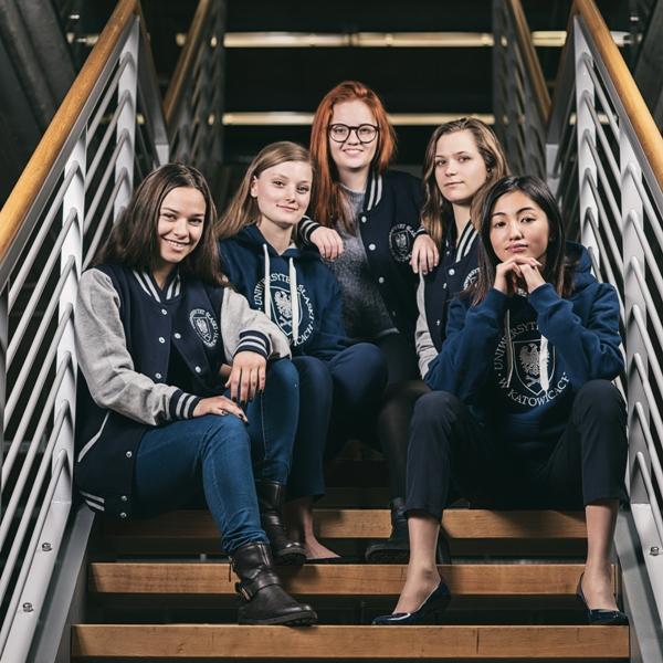 Grupa kobiet siedzących na schodachw bibliotece