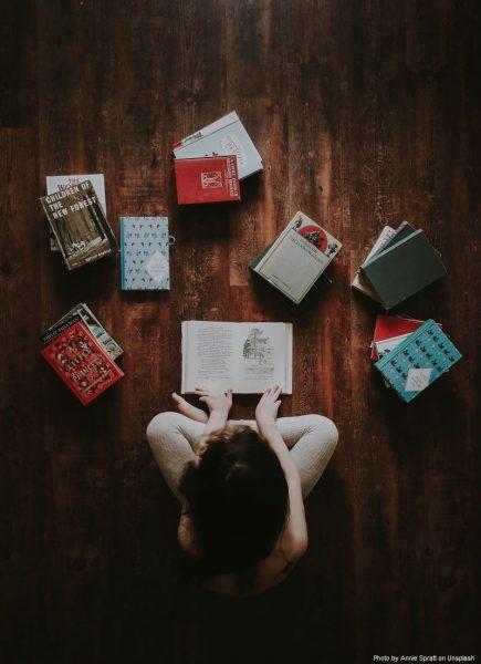 Dziewczynka siedzi na podłodze i czyta książki