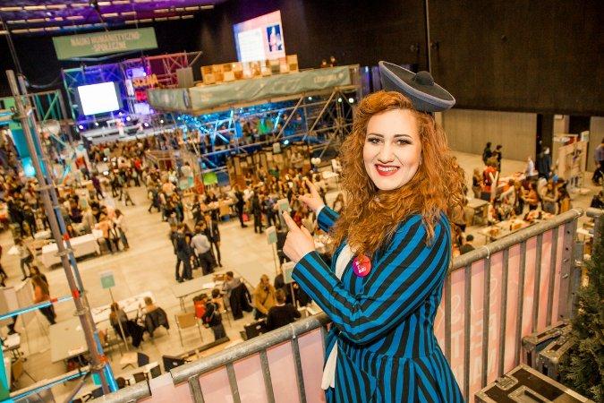 Rudowłosa kobieta w czapce przypominającej kształt katowickiego Spodka w hali pełnej ludzi