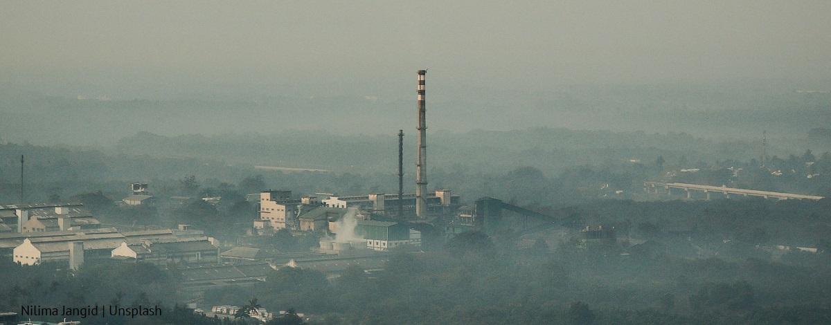 Smog w miejscowości, widoczna fabryka z wysokim kominem