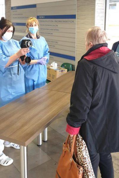 pracownicy medyczni mierząc pacjentom temperaturę za pomocą kamery termowizyjnej