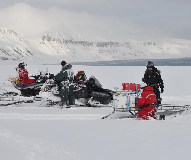 Kilkoro naukowców na Spitsbergenie ubranych w czerwone i czarne kombinezony, na skuterach śnieżnych