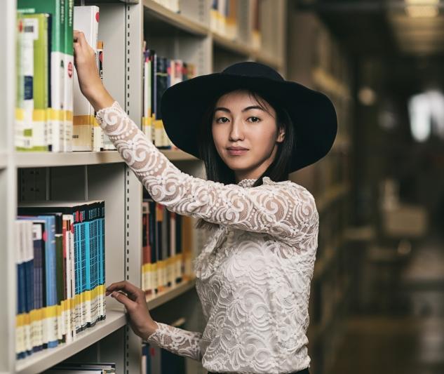 Młoda kobieta w kapeluszu stoi przy półce z książkami