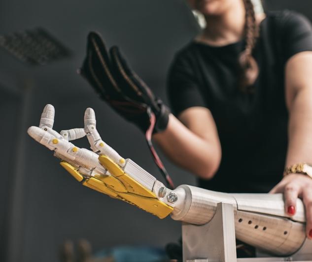 Człowiek steruje ruchami robota, na zdjęciu widoczna jest dłoń człowieka nad dłonią robota