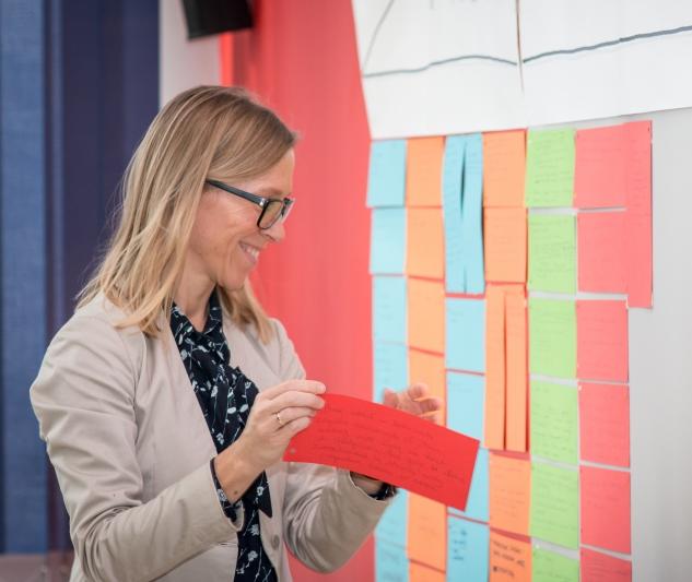 Kobieta stająca z czerwoną kartką przy tablicy, na której poprzypinanych jest wiele innych kartek