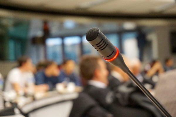 zdjęcie mikrofonu, w tle uczestnicy konferencji