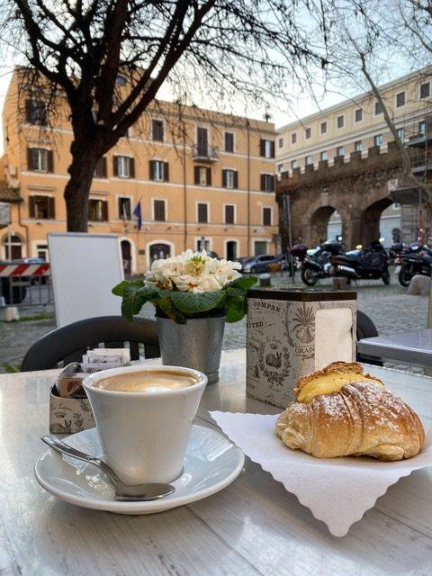 Kawa i rogalik w ogródku kawiarnianym w Rzymie