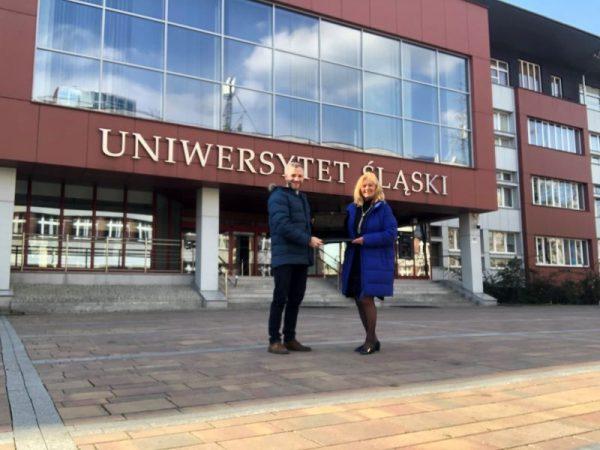Dr Tomasz Huk i dr Anna Watoła trzymają laptopa, w tle budynek rektoratu Uniwersytetu Śląskiego w Katowicach