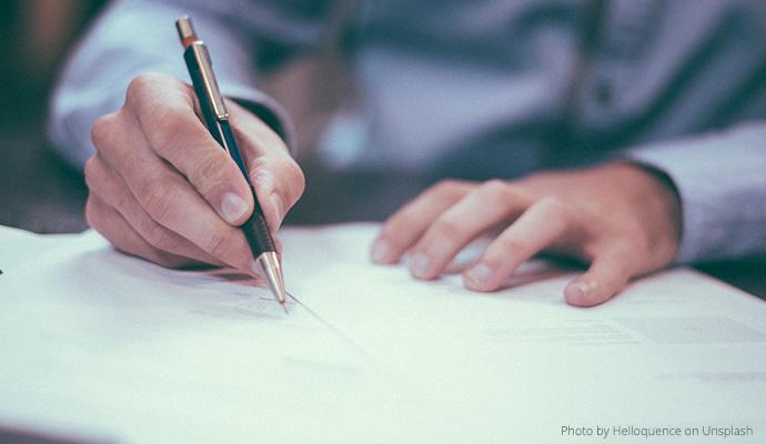 Osoba podpisująca dokumenty, zbliżenie na dłonie/Person signing documents, close-up of hands