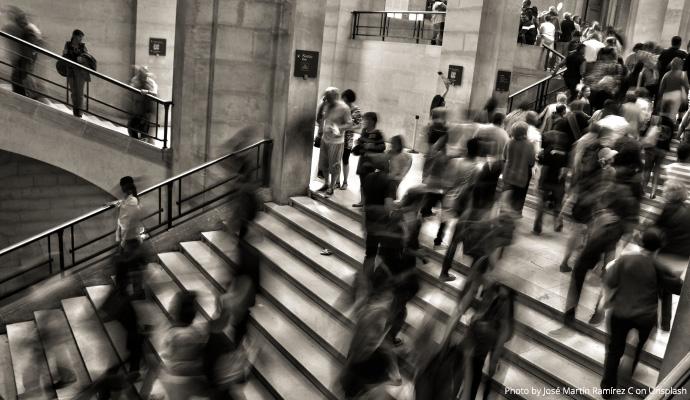 Liczna grupa osób przechodzących korytarzem. fot. Unsplash