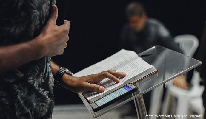 Osoba wygłaszająca wykład, zbliżenie na mównicę i otwartą książkę. Fot. Nycholas Benaia on Unsplash //Person giving a lecture, close-up of the platform and open book