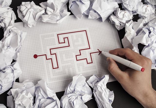 Ręka człowieka rysuje na papierze drogę wyjścia z labiryntu bordowym flamastrem