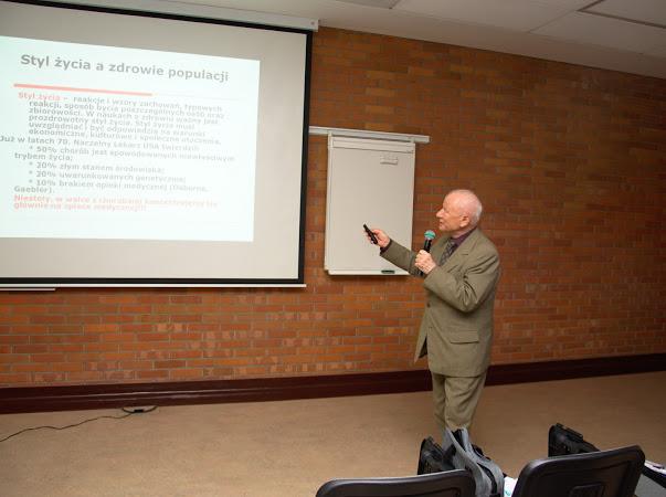 Prelegent wskazuje na ekran rzutnika, na którym wyświetlana jest prezentacja