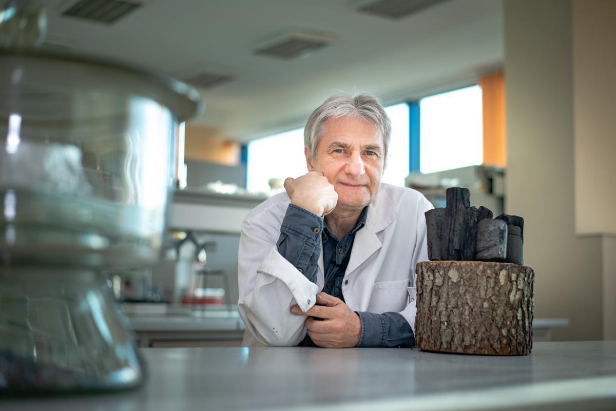 Naukowiec siedzący w laboratorium, przed nim kilka kawałków węgla