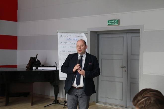 Mężczyzna w garniturze, przemawia, trzyma mikrofon