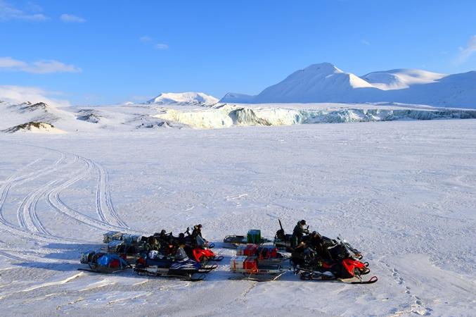Zdjęcie lodowca, naukowcy i skutery ze sprzętem