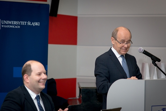 Dwóch mężczyzn, jeden przemawia, drugi siedzi przy stole