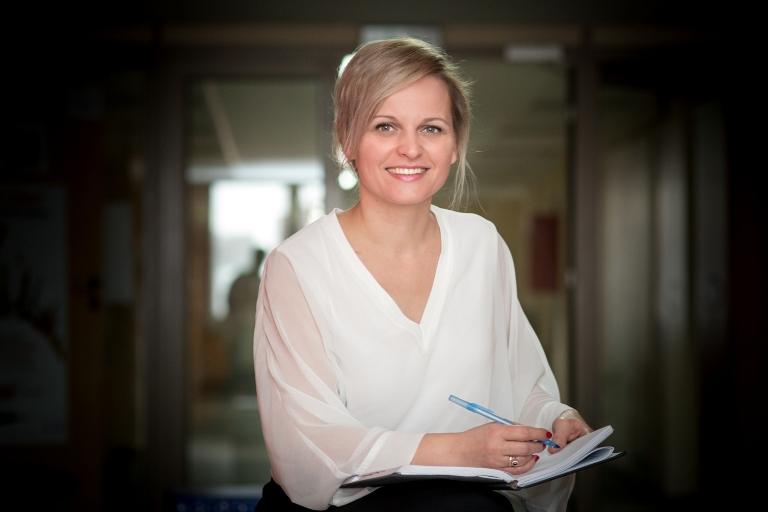 Zdjęcie portretowe dr Soni Szramek-Karcz – kobieta trzymająca notes z długopisem, patrząca w kadr