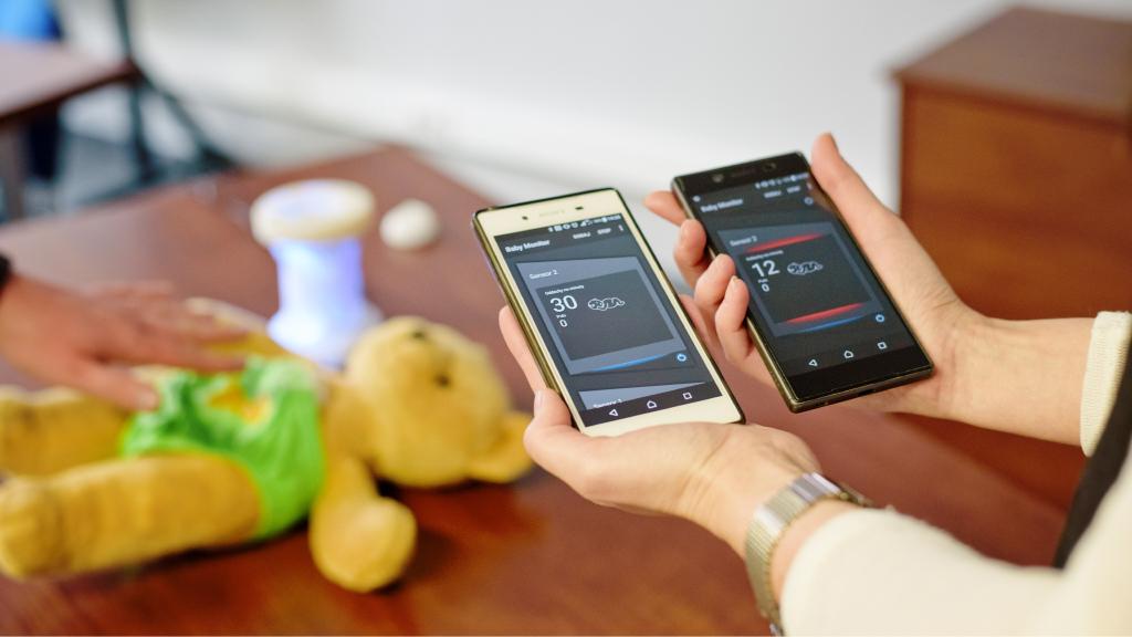 Prezentacja aplikacji monitora oddechu. W tle pluszowy miś oraz stacja bazowa.