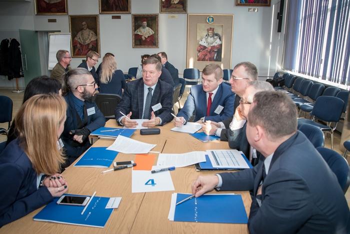 Osiem osób siedzących i rozmawiających przy stole