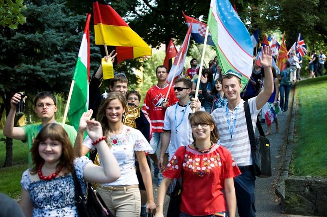 Uczestnicy Szkoły Języka i Kultury Polskiej (młodzi ludzie z flagami różnych krajów)