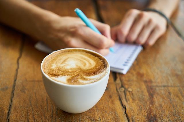 Na pierwszym planie kawa, na drugim ręka człowieka zapisującego coś długopisem w notesie