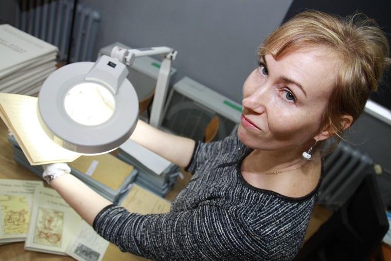 Dr Agnieszka Pieńczak w Pracowni Polskiego Atlasu Etnograficznego prezentuje jeden z zielników pod lupą