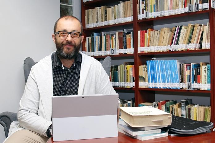 Dr hab. prof. UŚ Przemysław Marciniak z Wydziału Filologicznego UŚ siedzący przy stole, na którym znajdują się książki oraz sprzęt komputerowy