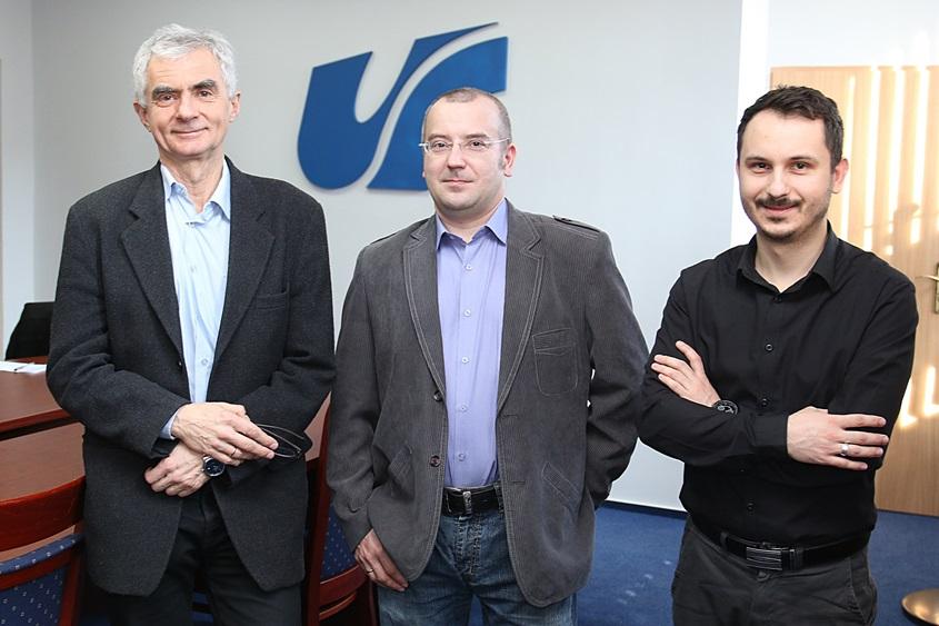 Trzej mężczyźni stoją na tle logo Uniwersytetu Śląskiego