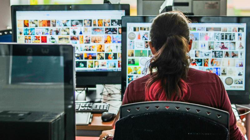 Zdjęcie: osoba pracująca przy komputerze (ujęcie z tyłu)
