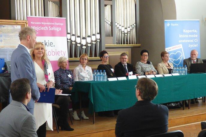 Uczestnicy konferencji, kilka osób na widowni i siedzących przy stole