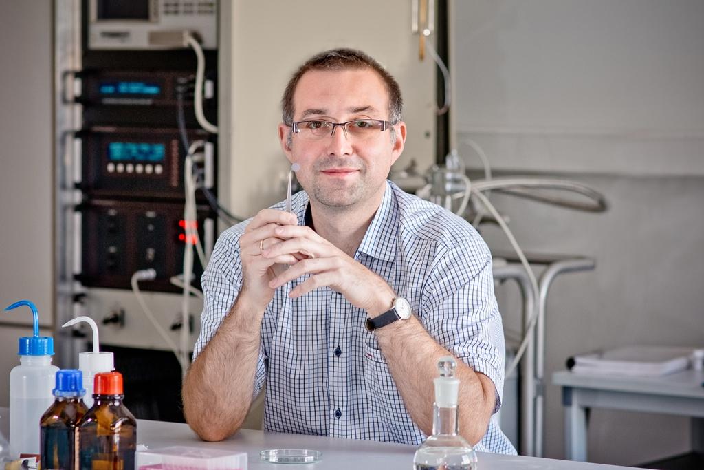 Dr hab. prof. US Kamil Kamiński trzyma materiał porowaty