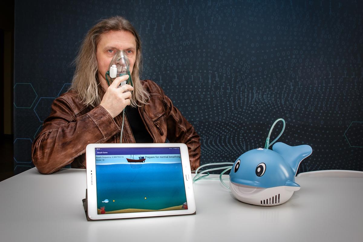 Mężczyzna w masce inhalacyjnej, przed nim znajduje się tablet i inhalator