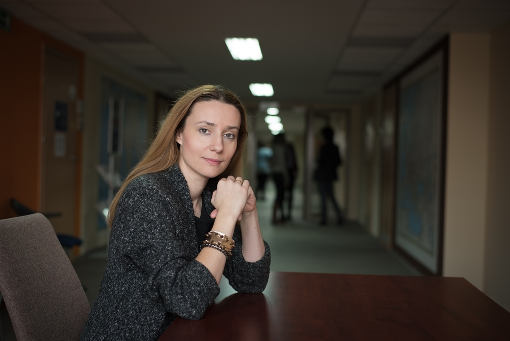 Dr Katarzyna Ślebarska siedzi przy stoliku, ręce opiera na stoliku, spogląda prosto w kadr