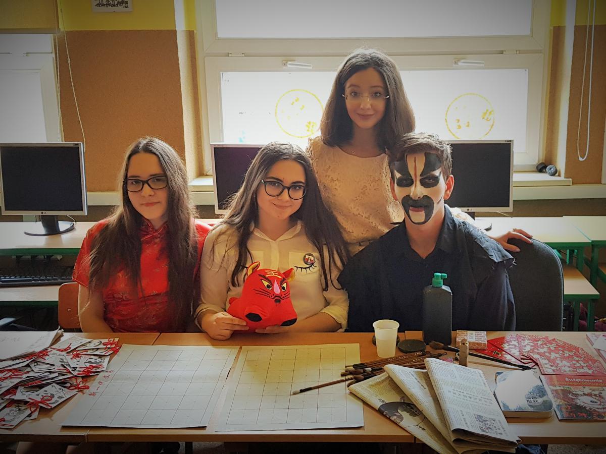3 osoby, młodzież, 3 dziewczyny, 1 chłopak z pomalowaną twarzą. Siedzą przy stole.