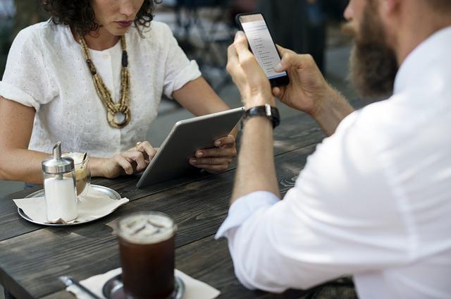 Dwoje ludzi siedzi w kawiarni. Ona przegląda strony internetowe na tablecie, on na smartfonie