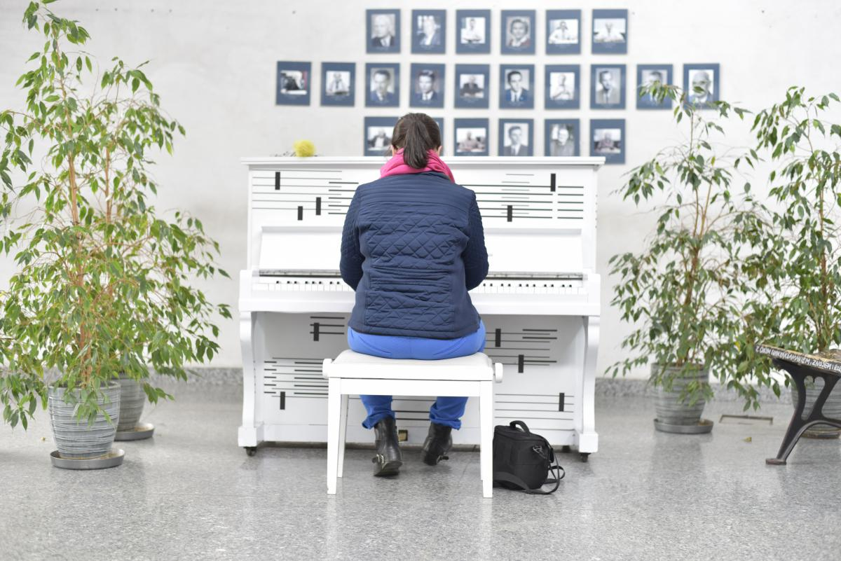 Pianino stojące w holu Wydziału Prawa i Administracji UŚ, osoba grająca
