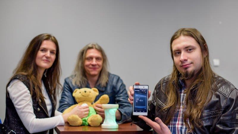 Troje ludzie, kobieta oraz mężczyzna trzymają misia, na pierwszym planie mężczyzna prezentujący aplikację mobilną na smartfonie