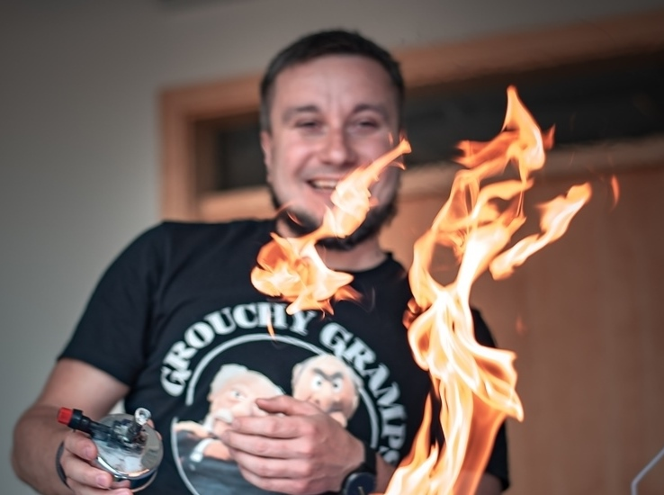 Mężczyzna, przed którym znajduje się płomień ognia